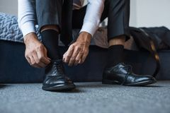 Cropped shot of man tying laces on black. Leather shoes Stock Photo
