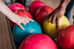 cropped shot of man and woman taking bowling balls stock photo