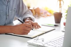 Cropped shot a Man writing on notebook paper on workplace. royalty free stock image