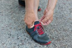 Cropped shot of mature man`s hands tights running shoes laces, stands on asphalt before morning run, recreats outdoor in rural are. A. Male runner ties Royalty Free Stock Photography