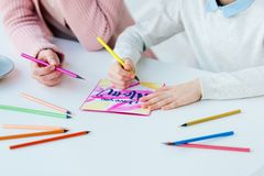 Cropped shot of mother and daughter making greeting postcard together. At table royalty free stock photography