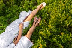 Cropped shot of mother and daughter in white dresses lying. On green grass royalty free stock photos