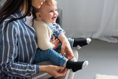 Cropped shot of mother dressing cheerful little baby on sofa. At home stock images