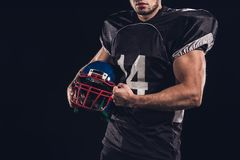 cropped shot of muscular american football player holding helmet