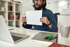 Free Cropped Shot Of Male Teacher Wearing Eyeglasses Showing A Blank Sheet Of Paper At Web Camera While Giving Online Lesson Royalty Free Stock Images - 189108799