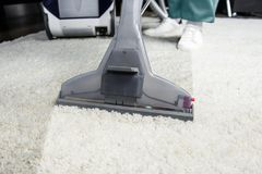 cropped shot of person cleaning white carpet with professional vacuum