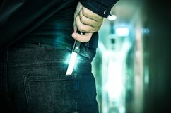 Cropped shot of a person hiding hand made knife behind his back. Cropped shot of a person hiding a hand made knife behind his back, concept of conflict and Royalty Free Stock Photos