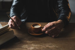 Cropped shot of person holding pencil and drinking coffee. At table Royalty Free Stock Photography