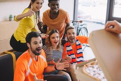 cropped shot of person holding pizza and excited group of multicultural friends stock image