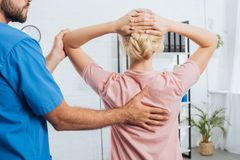 cropped shot of physiotherapist doing massage to woman