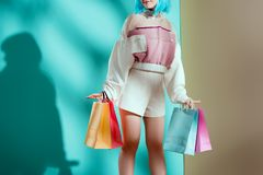 Cropped shot of pretty stylish girl. In blue wig holding shopping bags in studio royalty free stock photos