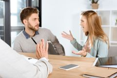 cropped shot of psychologist and emotional young couple quarreling stock photography