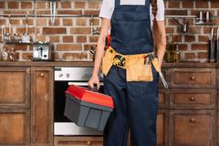 cropped shot of repairwoman with toolbox and toolbelt standing stock photo