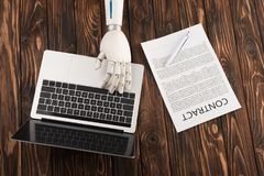 Cropped shot of robot working with laptop on wooden surface. With business contract royalty free stock image