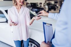 Salesman giving keys to happy woman royalty free stock images
