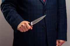 Cropped shot of senior man in suit holding knife Stock Photos