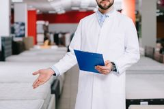 cropped shot of shop assistant with notepad pointing at orthopedic mattresses in white coat royalty free stock photography