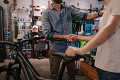Sports shop owner selling bicycle to customer. Cropped shot of shop owner giving a handshake to a customer after selling a bicycle Royalty Free Stock Image
