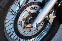 Cropped shot of the shot of the motorcycle forks, tire and fron. T wheel. Disk brake system on a motorcycle. Freedom and travel concept stock photos