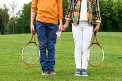 Cropped shot of siblings with badminton racquets holding hands and standing. On green grass royalty free stock images