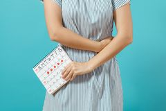 Cropped shot sickness woman in blue dress holding periods calendar for checking menstruation days put hand on tummy. Isolated on blue background. Medical royalty free stock photography