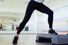 Cropped shot of skinny woman legs doing step aerobics. In gym. Wearing black sneakers for gym Royalty Free Stock Image
