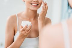 Cropped shot of smiling girl holding container and applying face cream at mirror. In bathroom stock images