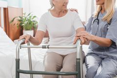 Cropped shot of smiling senior woman. Cropped shot of smiling senior women with walker and nurse holding hands royalty free stock photography
