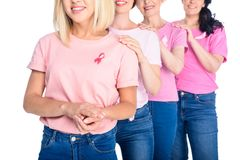 Women in pink t-shirts with ribbons. Cropped shot of smiling women in pink t-shirts with ribbons standing together isolated on white Royalty Free Stock Photo