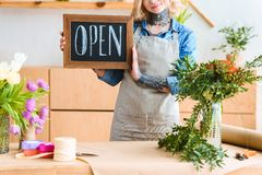 Cropped shot of smiling young florist holding sign open. In flower shop royalty free stock image