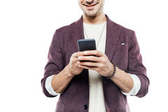 Cropped shot of smiling young man using smartphone Royalty Free Stock Photos