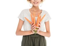 Cropped shot of smiling young woman holding ripe carrots. Isolated on white Stock Photos