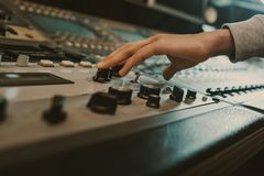 Cropped shot of sound producer touching knobs. On recording equipment Royalty Free Stock Image
