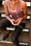 Cropped shot of sports woman texting message. On her electronic device, sitting on stairs Stock Images
