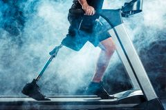 Cropped shot of sportsman with leg prosthesis training. On treadmill royalty free stock photography