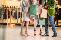 Cropped shot of stylish multiethnic people holding paper bags in shopping mall Royalty Free Stock Photos