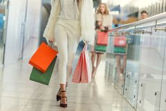 Cropped shot of stylish woman with paper bags walking by shopping mall Stock Photos