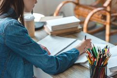 Cropped shot of teenage girl writing in notebook while studying. At home royalty free stock images
