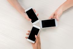 cropped shot of teenagers holding smartphones with blank screens stock photo