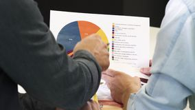 Cropped shot of two businessmen discussing printed diagram. Cropped rearview close up of two business colleagues having coffee at the office examining printed stock footage