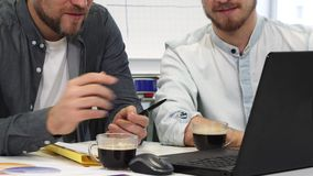 Cropped shot of two male business colleagues having coffee discussing work. Cropped shot of a mature bearded businessman and his younger colleague working on the stock video footage