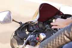 Cropped shot of unrecognizable active female motorcyclist tries to start engine, turns on key, covers long distance on road, wears stock images