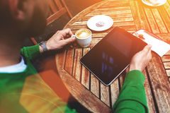 Cropped shot view of a businessman reading last news on touch pad during breakfast in sidewalk coffee shop, Stock Photography