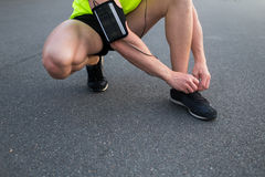 Cropped shot view of man's hands with armband tie the laces on sneakers after intensive jogging outdoors Royalty Free Stock Image