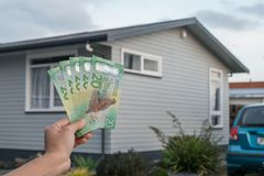 Cropped shot view of men hand holding New Zealand dollar bills in front of a single house in New Zealand. Conceptual of Real estate business. New Zealand dollar royalty free stock photo