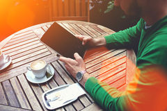 Cropped shot view of a smart male student reading news on digital tablet while breakfast in sidewalk cafe. Man holding touch pad with copy space screen for your Royalty Free Stock Photography