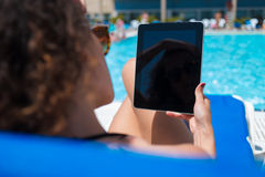 Cropped shot view of woman reading book on touch pad while relaxing near pool during summer vacation Stock Photos