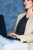 Cropped shot view of young woman working on laptop lying on her knees. stock photography