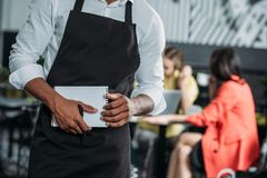 Cropped shot of waiter in apron with notepad. At cafe Stock Photos