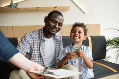 Father and son paying bill Stock Images